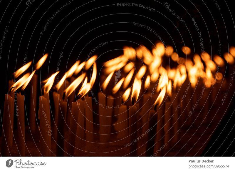 Zahlreiche flackernde Gebetskerzen, monochrom Kerzen beten Flackern Beten Hoffnung Kerzenschein Glaube Religion glauben Frieden Flammen stimmungsvoll brennend