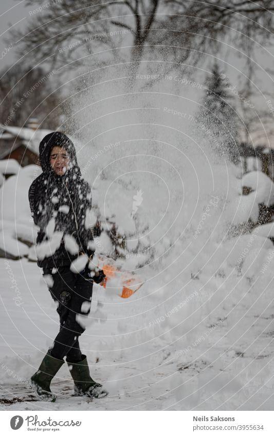 Menschen freuen sich immer über den ersten Schnee / den größten Schneesturm seit ein paar Jahren Junge Reinigungsschnee genießend Winter kalt Außenaufnahme