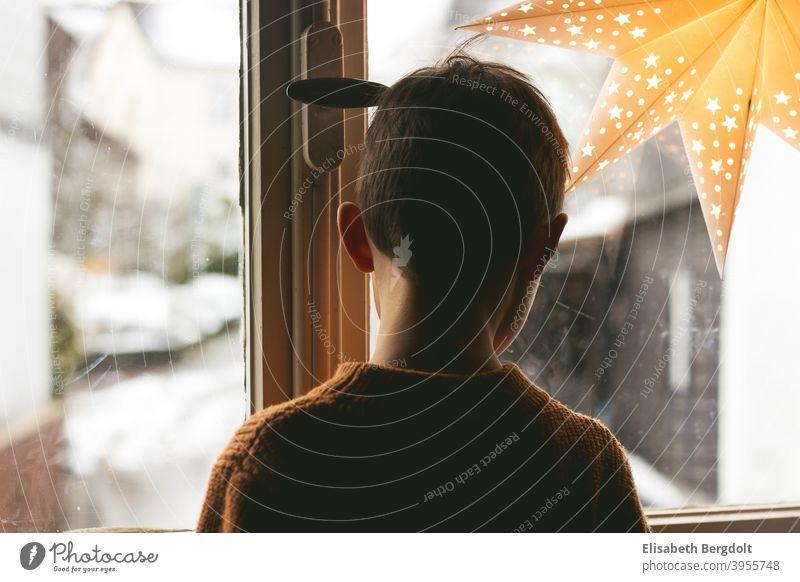 Kleiner Junge schaut aus dem Fenster, das mit einem leuchtendem Stern geschmückt ist. Rückenansicht 30er Jahre Fenster Leuchtender Stern Sehnsüchtig Wartend
