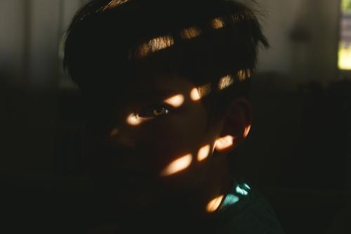 Kleiner Junge, mit Blick in die Kamera und Lichteinfall der Sonne auf das Auge, was durch die kleinen Öffnungen der Rollläden hindurchgeht Lichteinfall Auge