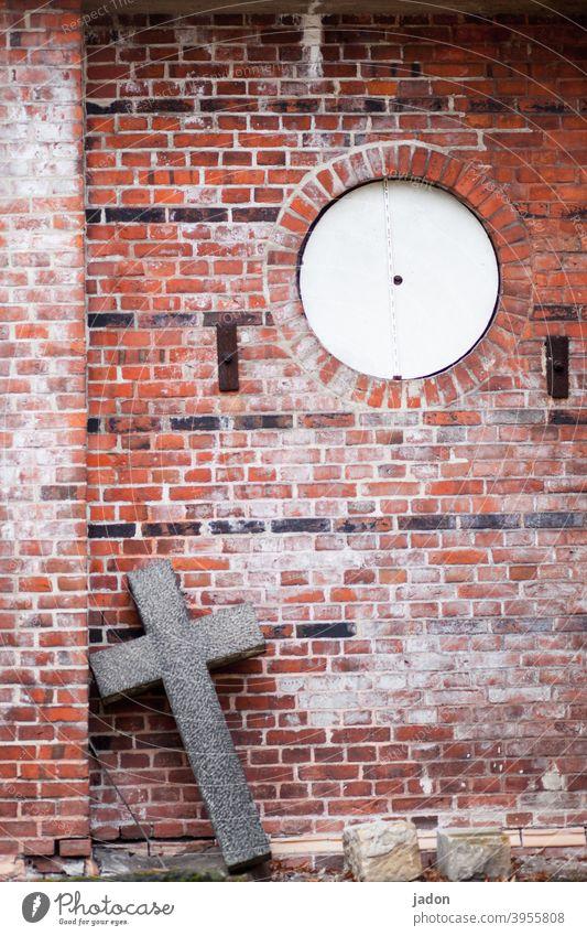 christliches kreuz aus stein lehnt schräg an einer mauer, welche eine runde öffnung hat. Religion & Glaube Kreuz Christliches Kreuz Christentum Kirche