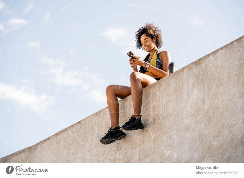 Sportliche Frau, die ihr Mobiltelefon im Freien benutzt. Athlet Fitness Mobile Telefon Fitnessstudio ruhen sich[Akk] entspannen aktiv Porträt Apparatur
