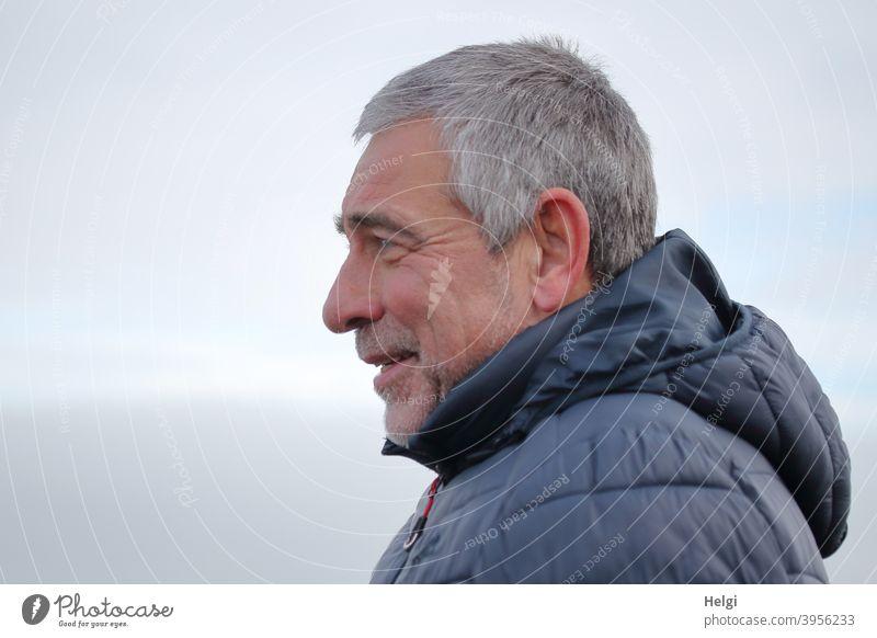 Porträt eines lächelnden Senioren im Profil mit grauen kurzen Haaren, Dreitagebart und blauer Winterjacke mit Kapuze Mensch Mann männlich kurzhaarig grauhaarig