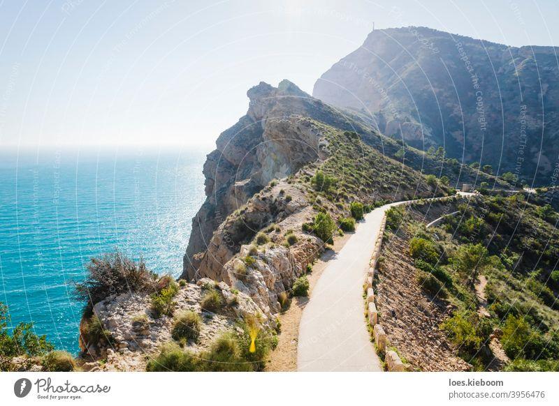 Landschaftlich reizvoller Wanderweg entlang steiler, mit Büschen bewachsener Klippen am Meer im Naturpark 'Serra Gelada' in Albir, Spanien albir mediterran Ufer