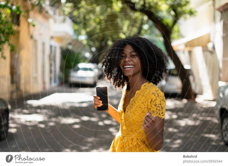 Junge schwarze Frau mit lockigem Haar, in gelbem Kleid und mit Stilen, Haltung, lachend, glücklich Individualität Ethnizität Haut Lächeln Frisur Nachricht