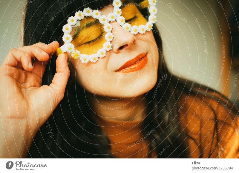 Frau mit Blümchen-Sonnenbrille im Sonnenlicht. Retrostimmung, Optimismus gute Laune und Sommer. Sommerstimmung Frühling Sonnenschein farbenfroh gelb orange