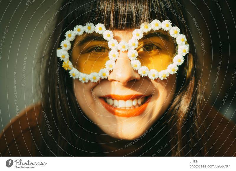 Lachende Frau mit Blümchen-Sonnenbrille im Sonnenlicht. Retrostimmung, gute Laune, Optimismus und Sommer. Sommerstimmung Frühling Sonnenschein farbenfroh gelb