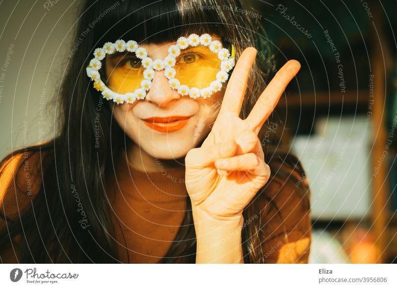 Junge brünette Frau mit sommerlicher Blümchensonnenbrille zeigt das Victoryzeichen Hippie Sonnenbrille pazifistisch Peace peacezeichen zwei ausgestreckte Finger