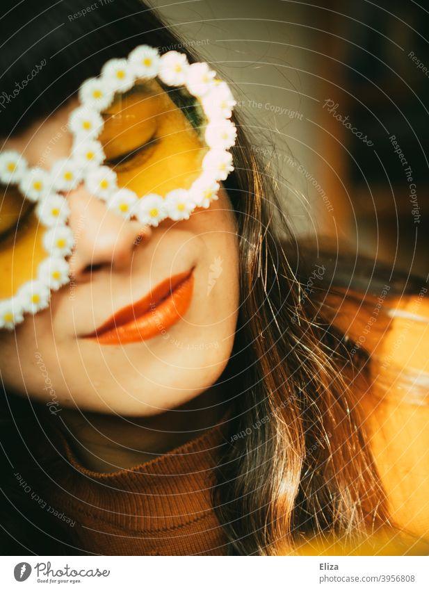 Frau mit Blümchen-Sonnenbrille im Sonnenlicht. Retrostimmung, Optimismus, gute Laune und Sommer. Sommerstimmung Frühling Sonnenschein farbenfroh gelb orange