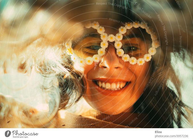 Lächelnde Frau mit lustiger Blümchen-Sonnenbrille guckt vornübergebeugt in die Kamera gute Laune Freude Brille Hippie nach unten gucken Haare lange Haare