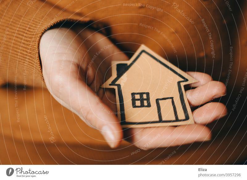 Eine Person hält ein gemaltes Haus in der Hand Zuhause Hauskauf Immobilie Eigenheim kaufen neues Zuhause Hypothek halten Geborgenheit wohnen Kapitalanlage