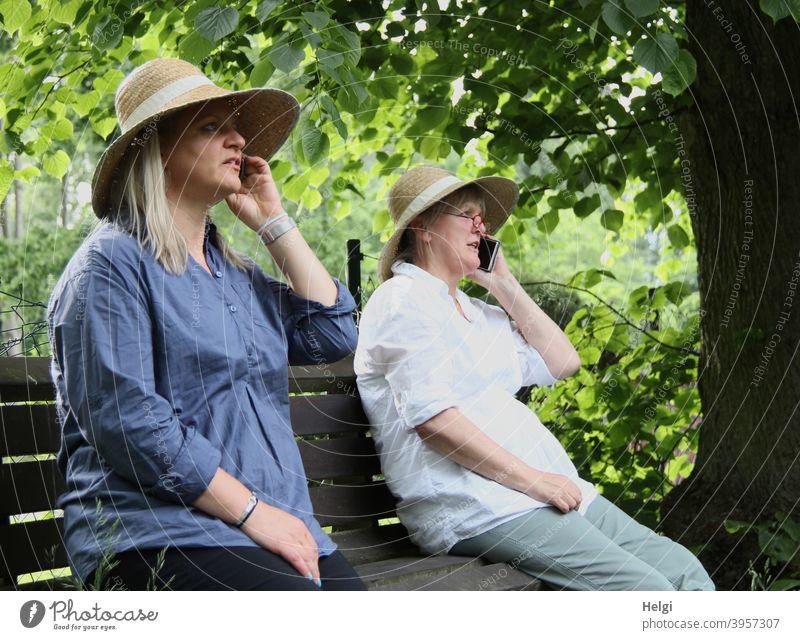"""""""Wurde wirklich Zeit,dass wir uns wiedersehen! Ich freu mich!"""" - Zwei Frauen mit Hut sitzen auf einer Bank und telefonieren miteinander Mensch Seniorin Baum"""