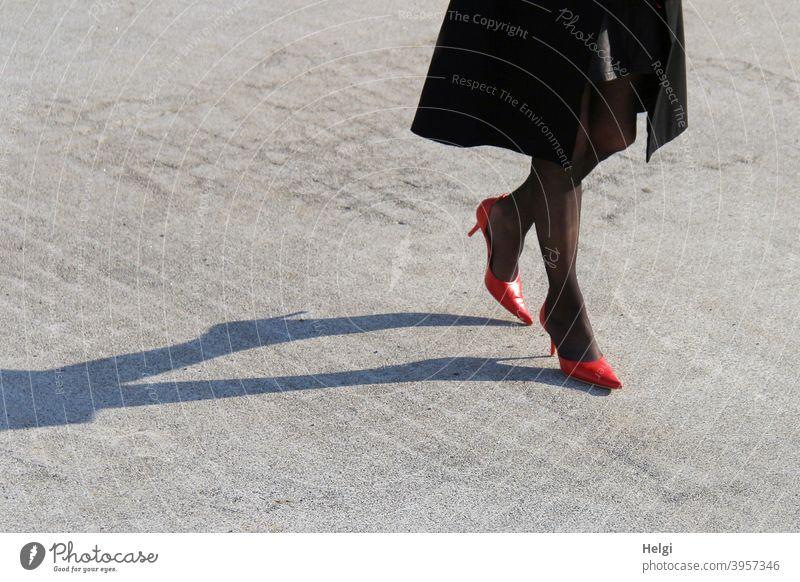 Beine einer eleganten Dame in roten Pumps und schwarzen Strümpfen sowie schwarzem Mantel mit langem Schatten auf Steinboden Frau Schuhe Licht gehen