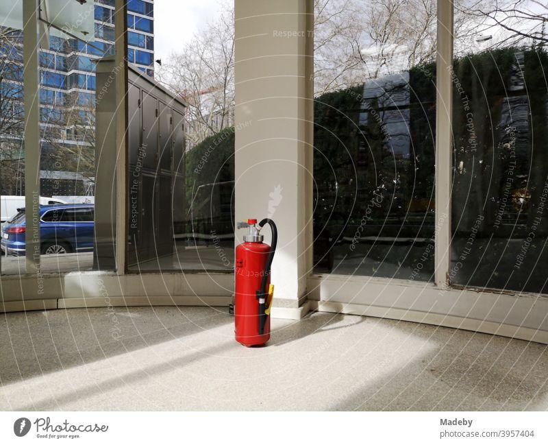 Roter Feuerlöscher im Foyer eines denkmalgeschützten Bürogebäude der Fünfzigerjahre im Westend von Frankfurt am Main in Hessen Knallrot Sicherheit Brandschutz