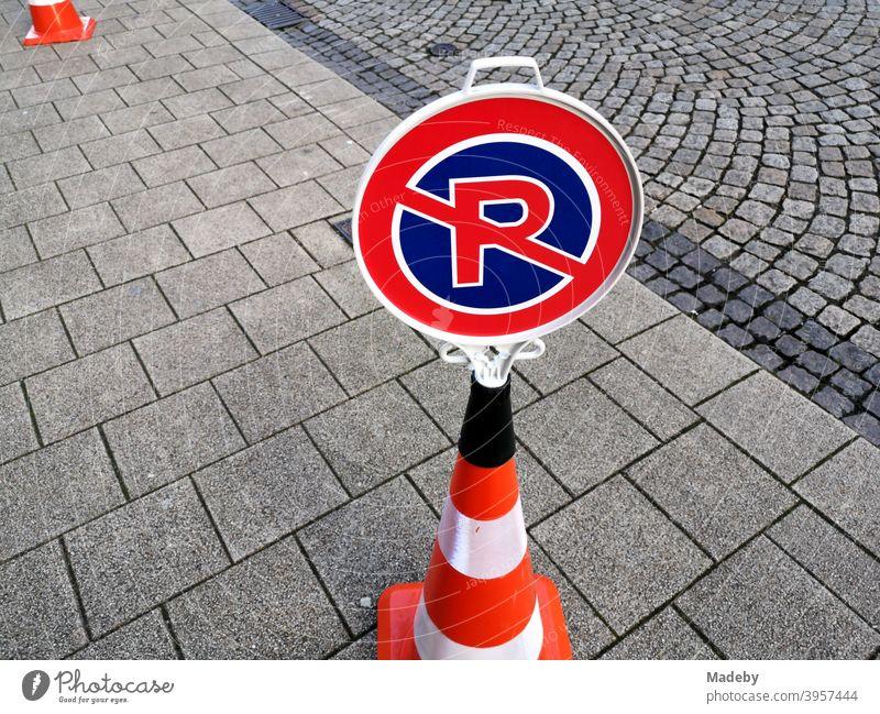 Tragbares inoffizielles Verkehrszeichen für Parkverbot und Halteverbot auf einem Lübecker Hütchen auf grauem Straßenpflaster Verkehrsschild Parkverfbot
