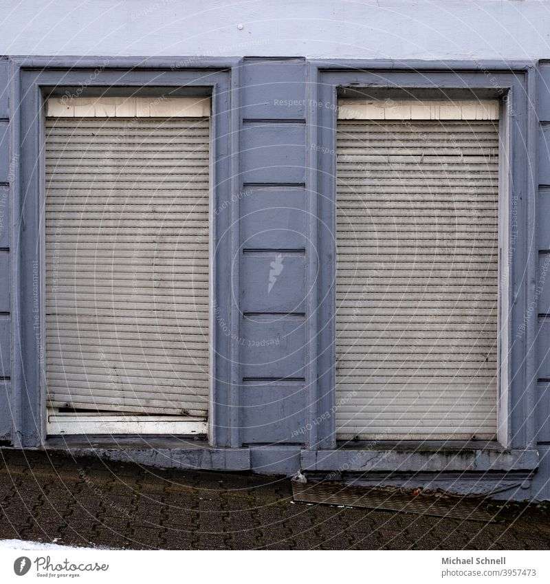 Alte, graue Rolladen an einem alten Haus blau geschlossen Fenster Fassade trist Wand Menschenleer Rollladen Verfall