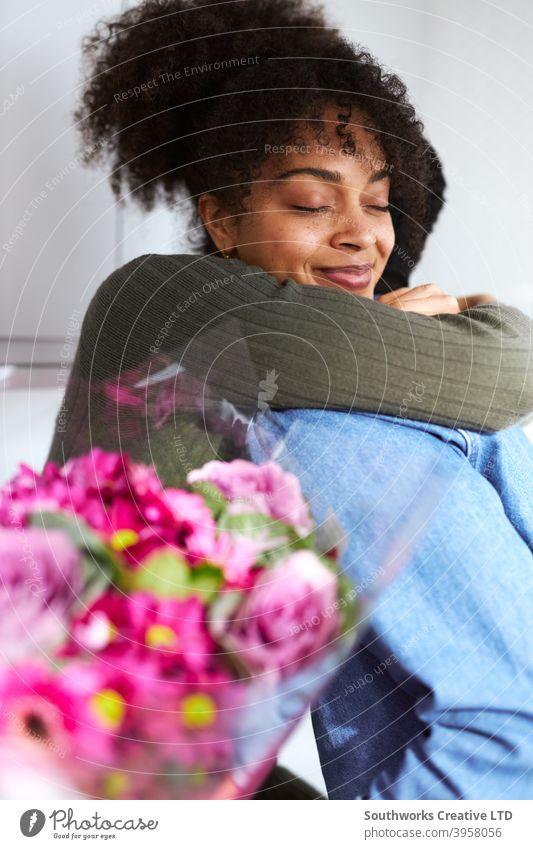 Romantisches Paar zu Hause mit Mann überraschend Frau mit Blumenstrauß feiern valentines Tag, Geburtstag oder Jahrestag und sie gibt ihm umarmen junges Paar