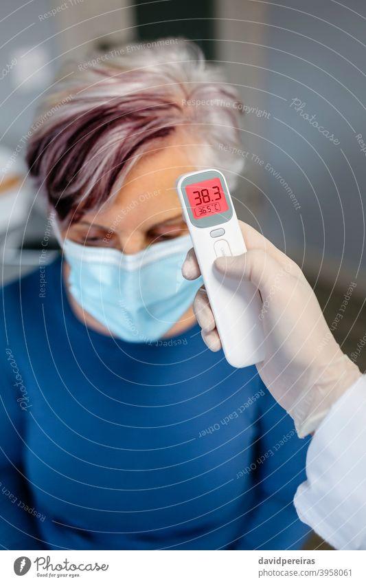 Ältere Frau mit Fieber, deren Temperatur von ihrem Arzt gemessen wird Senior berührungsloses Thermometer covid-19 Symptom Messung Schutzmaske Überprüfung