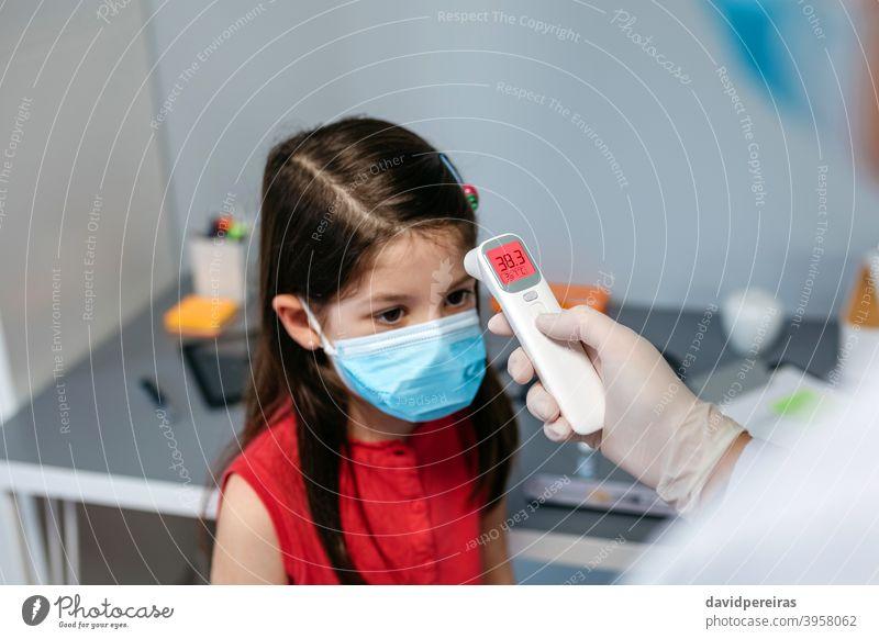 Mädchen mit Fieber, dessen Temperatur vom Arzt gemessen wird Infrarot-Thermometer Symptom Coronavirus Schutzmaske Kind covid-19 krank kalt wenig digital