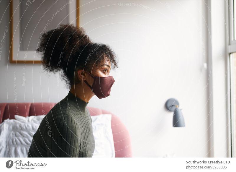 Frau trägt Gesichtsmaske im Schlafzimmer, bevor sie das Haus während der Gesundheitspandemie verlässt zu Hause Mundschutz Gesichtsbedeckung ppe anmachend
