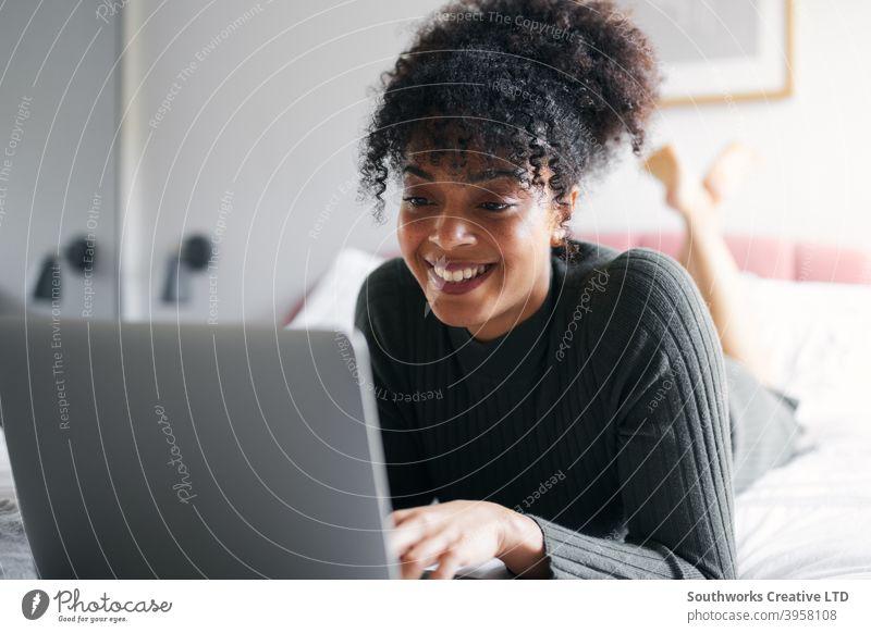 Frau liegend auf dem Bett arbeiten von zu Hause aus auf Laptop-Computer von zu Hause aus arbeiten Browsen WFH Sperrung covid-19 Coronavirus Schlafzimmer Lügen
