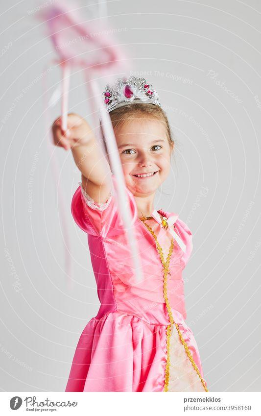 Kleines Mädchen genießt ihre Rolle der Prinzessin. Adorable niedlichen 5-6 Jahre altes Mädchen trägt rosa Prinzessin Kleid und Tiara hält Zauberstab Fee Kind