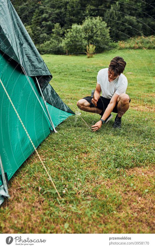 Junger Mann beim Aufbau eines Zeltes auf dem Campingplatz während der Sommerferien Reise Pfahl Zapfen Hammer Gras nach oben Einstellung Setzen Pitsching