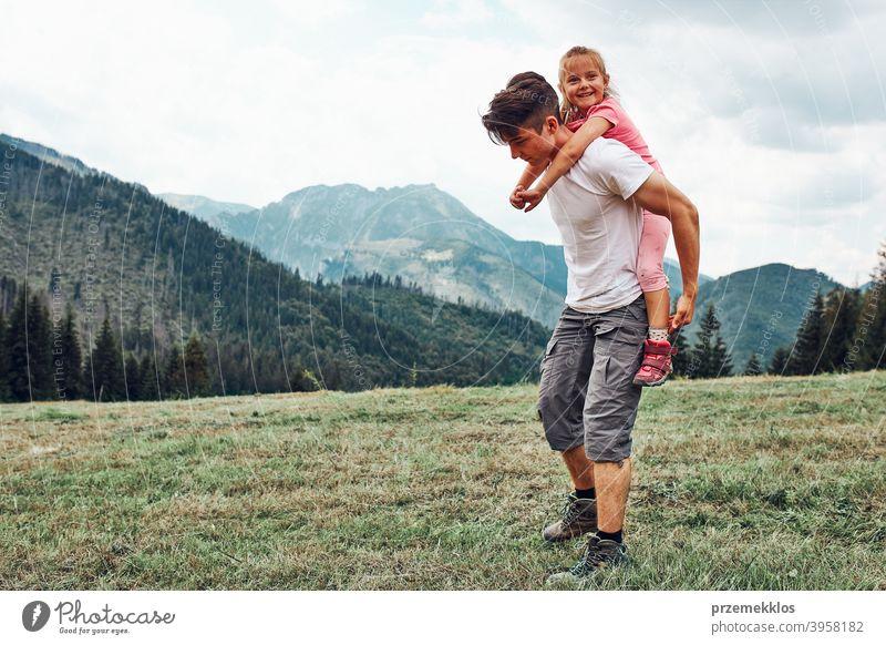 Junger Mann hält kleines Mädchen auf seinem Rücken. Kind spielt mit ihrem älteren Bruder reiten auf seinem Rücken genießen Sommertag zusammen Glück Aufregung