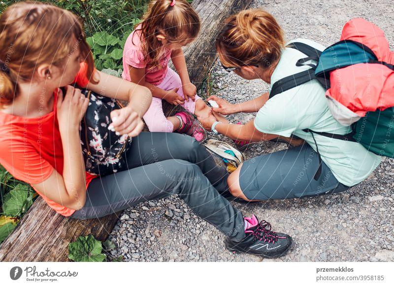 Mutter, die die Wunde am Knie ihrer kleinen Tochter mit Medizin im Spray verbindet. Der Unfall ereignete sich während des Sommerurlaubs der Familie Trekking