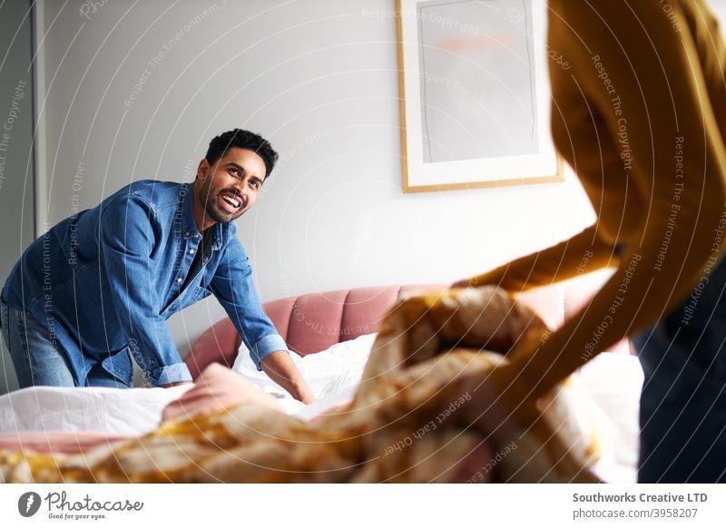 Junges Paar teilt sich die Hausarbeit und macht das Bett zu Hause zusammen junges Paar Bett machen Bettwäsche wechseln Arbeit Hilfe Zusammensein im Innenbereich