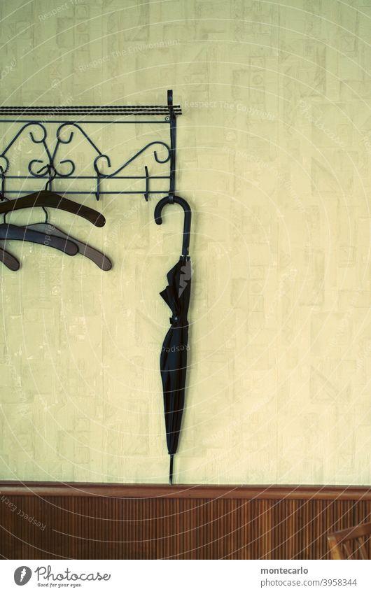 Ein Regenschirm hängt an einer Retro Garderobe Einfachheit sparsam minimalistisch Ordnung Stil Grafik u. Illustration Menschenleer Wand einfach aufhängen
