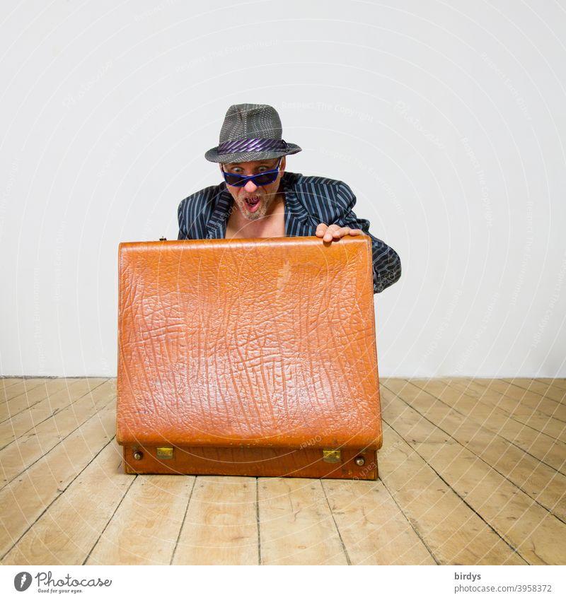 Mann im Anzug mit Hut und Sonnenbrille blickt sehr erstaunt in einen geöffneten alten Koffer. Überraschung Erstaunen Entsetzen Blick Inhalt Holzfußboden