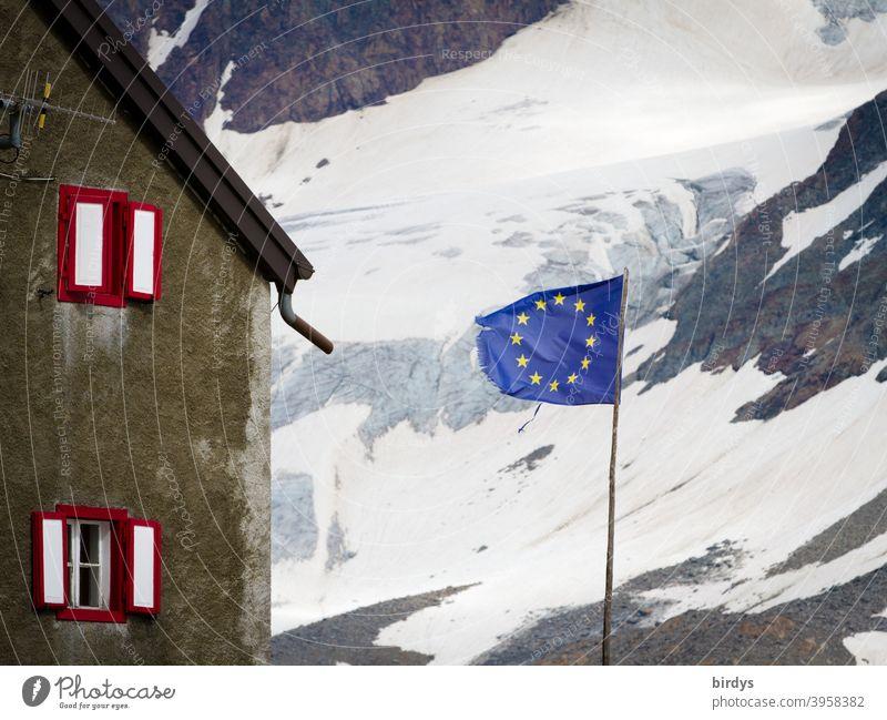 Flagge der europäischen Union vor einem Haus in den Bergen , im Hintergrund ein schneebedeckter Berghang . EU - Fahne Europäische Union Europafahne Alpen Schnee