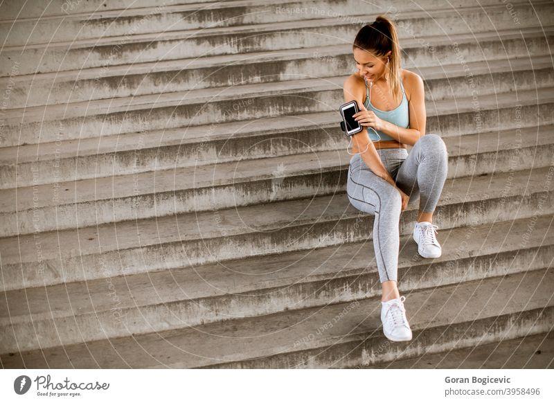 Fitness-Frau, die eine Pause vom Laufen macht, auf den Stufen sitzt und das Handy in der Armbinde verklagt jung Lifestyle urban Training Gesundheit Sport Sitzen