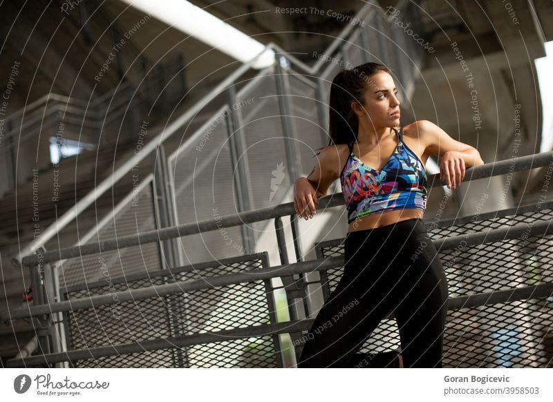Junge Fitness-Frau, die eine Pause vom Laufen in städtischer Umgebung macht Athlet schön Großstadt Stadtbild Beton Übung Behaarung Glück Gesundheit Freizeit