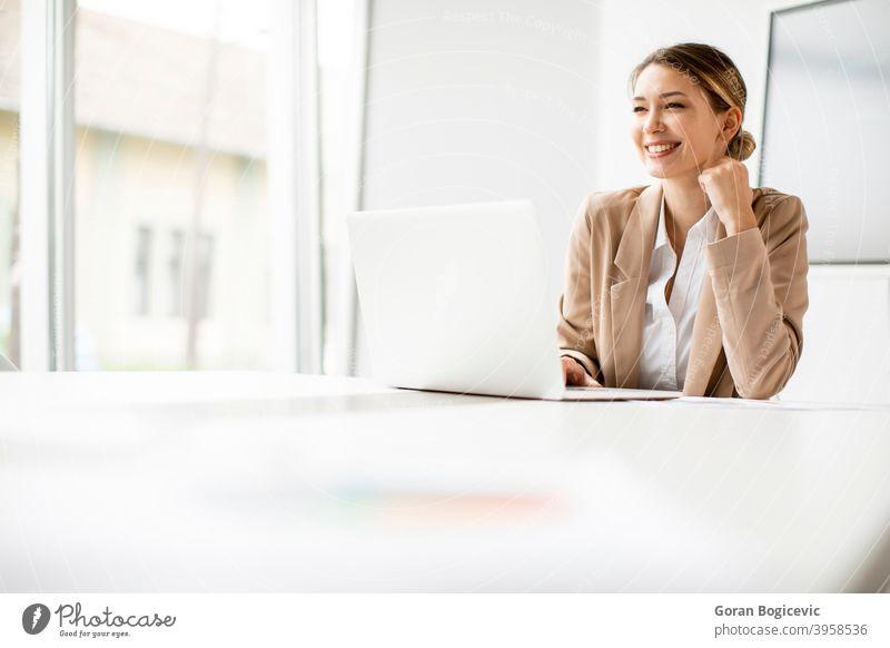 Junge Frau arbeitet am Laptop in hellem Büro mit großem Bildschirm hinter ihr Erwachsener attraktiv schön Business Kaukasier Mitteilung Computer selbstbewusst