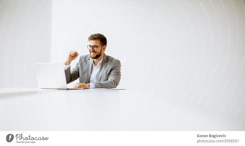 Junger Mann arbeitet am Laptop in hellem Büro Erwachsener attraktiv schön hinten Business Kaukasier Mitteilung Computer selbstbewusst Tag Schreibtisch elegant