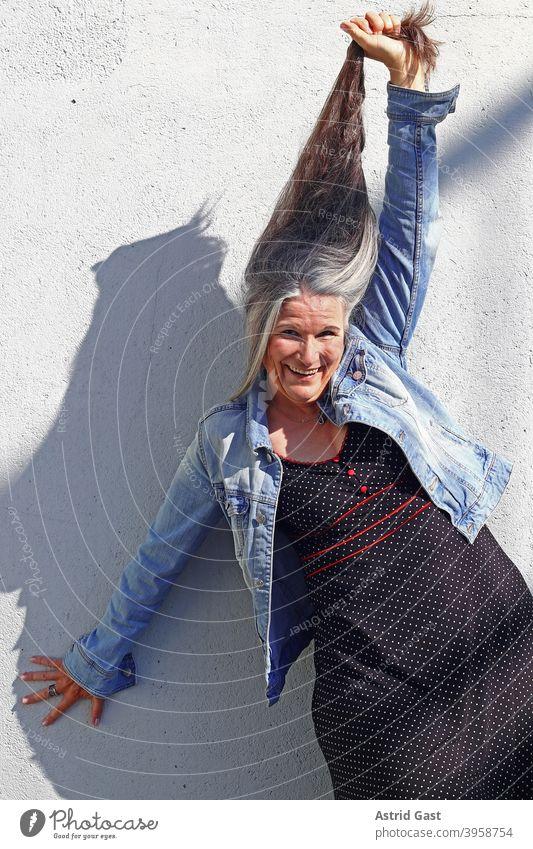 Eine ältere Frau streckt lachend ihr sehr langes graues Haar nach oben frau haare lange haare alter grauhaarig seniorin spaß freude lustig freuen graue haare