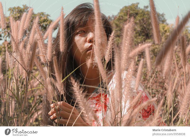 Schöne asiatische Mädchen unter der Wiese des Brunnens Gräser asiatische Frau konzeptionell natürlich Emotion Ruhe Windstille Glückseligkeit sonnig Sinnlichkeit