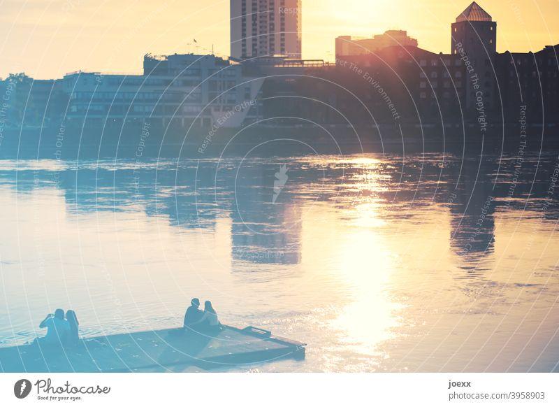 Zwei Paare sitzen entspannt am Wasser und genießen den Sonnenuntergang an der Skyline. VOR Corona Menschen Steg Fluss Ufer zusammen Sonnenlicht Sonnenstrahlen