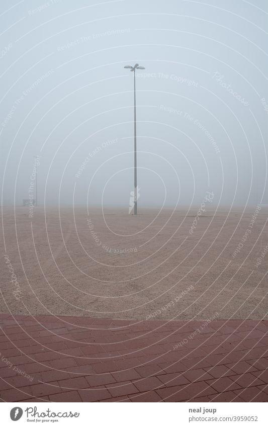Straßenlampe auf einer im Nebel verschwindenden Brachfläche; ein Parkplatz Außenaufnahme Stadt urban Brache Brachland Industrie Fläche morgen diffus Horizont