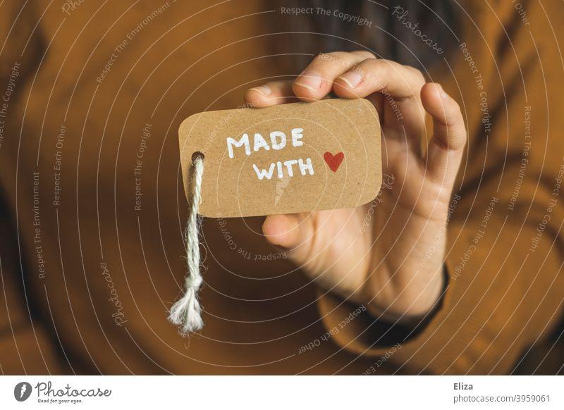 Person hält ein Etikett auf dem Made with love steht. made with love handarbeit liebevoll einkaufen Konsum lokal Kleinunternehmen selbstgemacht Schild