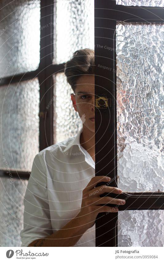 Porträt eines jungen Mannes in weißem Hemd in einem Wohnungsinterieur. Kaukasier Sitzen Erholung Bekleidung Amerikaner Haus entspannt Kontemplation Raum allein