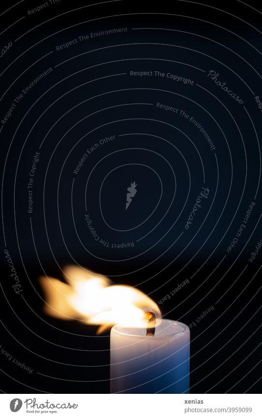 Die Flamme einer Kerze wird in der Dunkelheit vom Wind zur Seite gepustet Licht Feuer dunkel Kerzendocht brennen Kerzenschein Docht Kerzenflamme pusten blau