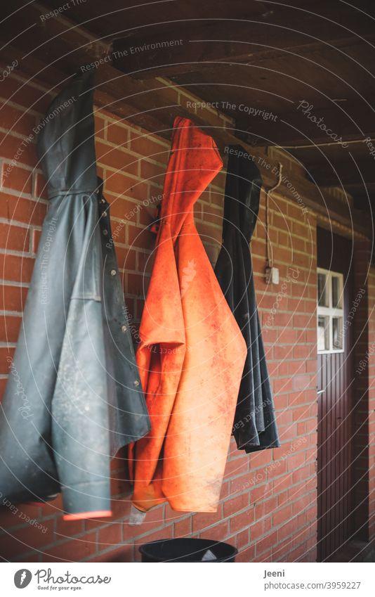 Beim Fischer im kleinen Fischerdorf hängen die Regenjacken draußen vor der Tür nebeneinander Regenmantel Fischereiwirtschaft Fischerhütte fischerhaus Kleidung