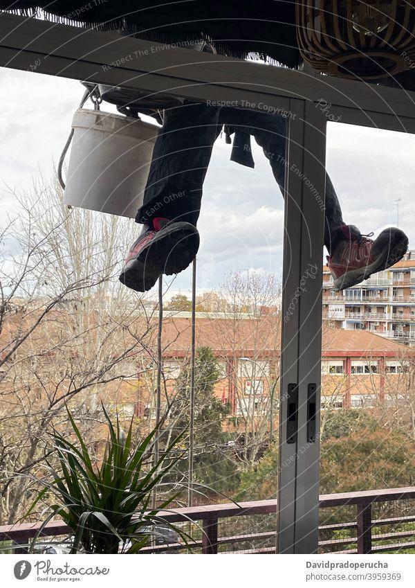Unbekannter Bergsteiger putzt Fenster eines Gebäudes industriell Alpinismus Sauberkeit Alpinist Waschen Glas wohnbedingt hängen Haus Außenseite Fassade Arbeit