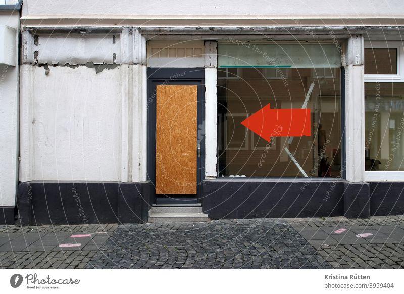 großer roter pfeil am schaufenster eines leeren geschäfts zeigt auf grobspanplatte in der tür laden osb-platte verlassen geschlossen leerstand geschäftsaufgabe