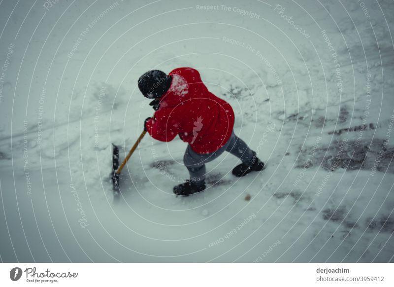 Eine Person mit roter Jacke und schwarzer Mütze , schiebt mit einer Schnee Schaufel den Schnee  mühsam und mit viel Kraft aus dem Weg. schnee räumen Winter kalt