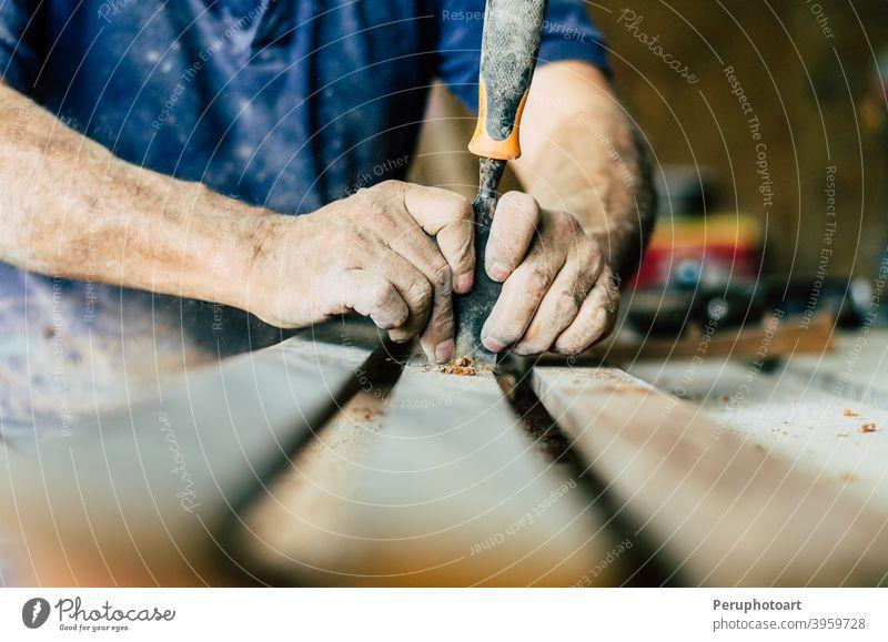 Professioneller Schreiner bei der Arbeit, er schnitzt Holz mit einem Holzbearbeitungswerkzeug, Hände Nahaufnahme, Zimmerei und Handwerkskunst Konzept