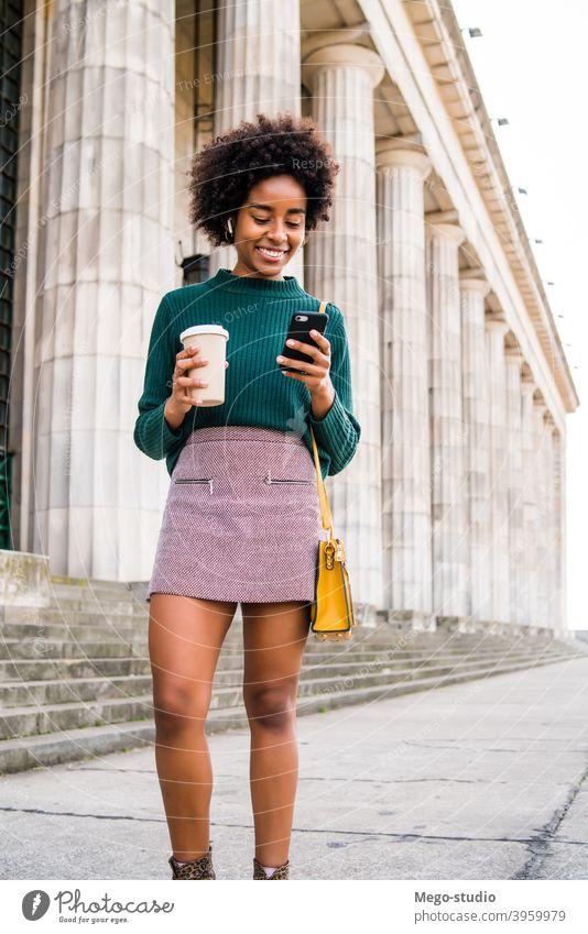 Geschäftsfrau, die ihr Mobiltelefon im Freien benutzt. Afro-Look Business Frau Mobile Telefon schwarz modern Stil brünett Apparatur positiv Konzept Anschluss